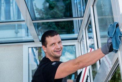Mitarbeiter reinigt Fensterscheibe